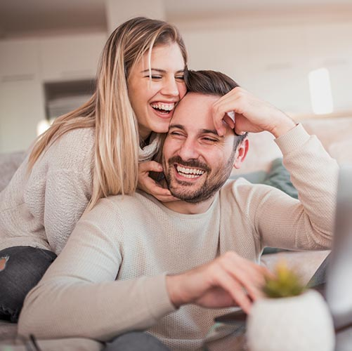 couple at home laughing on couch